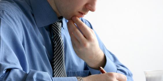 Mann bei der Zeugnisanalyse, Zeugniserstellung oder Zeugnisüberarbeitung